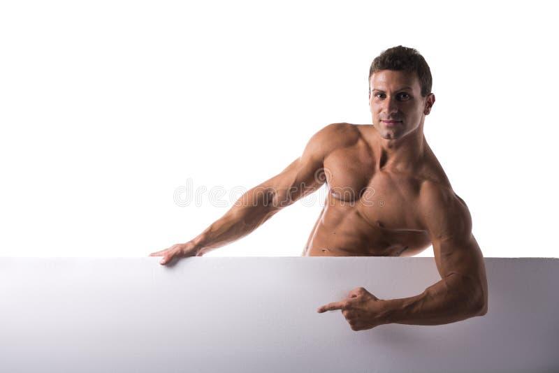 Stark muskulös shirtless ung man som rymmer ett vitt baner fotografering för bildbyråer
