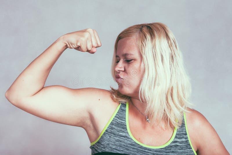 Stark muskulös sportig kvinna som böjer biceps arkivbilder