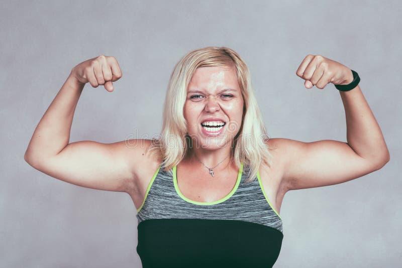 Stark muskulös sportig kvinna som böjer muskler royaltyfria foton
