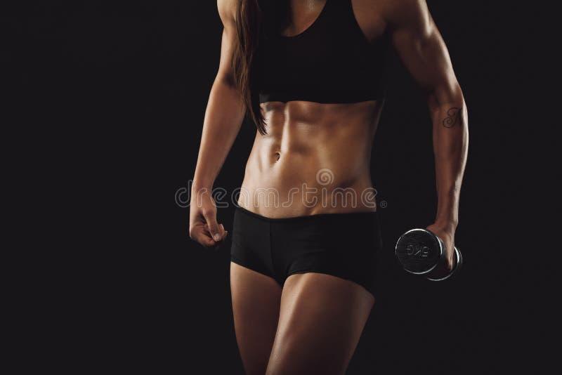 Stark och muskulös byggandekvinna som övar med hanteln royaltyfri foto