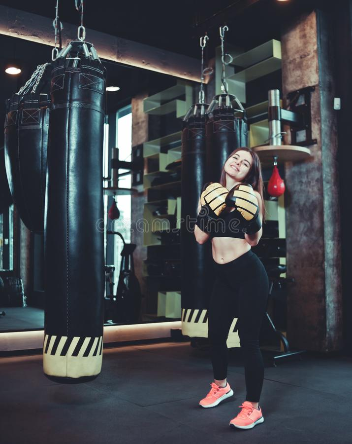 Stark och säker ung kvinna som poserar och ler i boxninghandskar royaltyfria bilder
