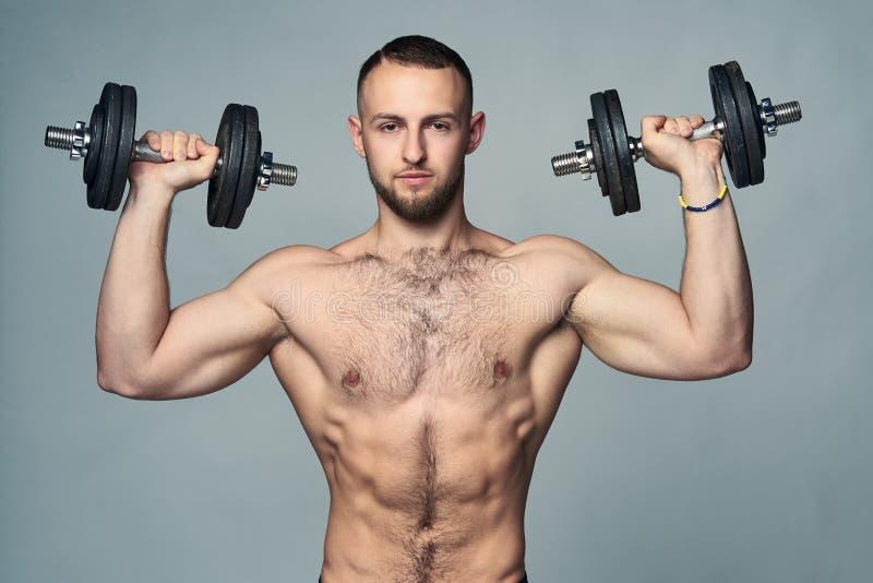 Stark shirtless sportman med isolerade hantlar arkivbilder