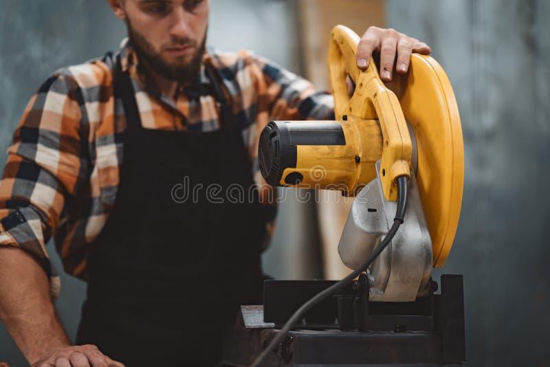 Stark skäggig man som arbetar på den elektriska vinkelformiga malande maskinen i metalworkingfabrik royaltyfri foto