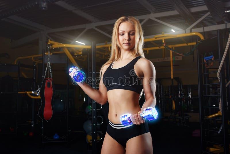 Stark sportig kvinnakroppsbyggare med den brunbrända kroppen som gör övningar med hanteln i idrottshallen Sportar och kondition N royaltyfri foto