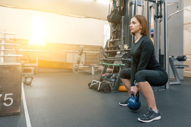 Stark ung konditionkvinnautbildning med tunga vikter i konditionidrottshall Sport kondition, bodybuilding, utbildning, livsstil o royaltyfria foton