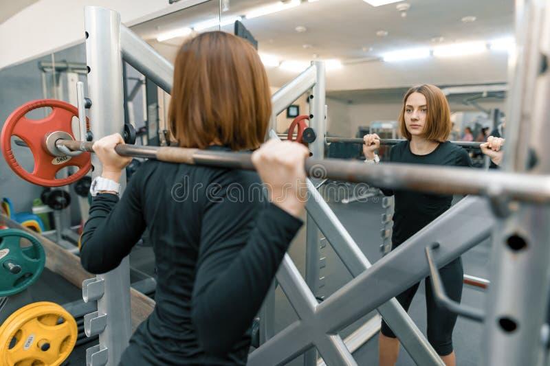 Stark ung kvinna som gör tungviktgenomkörare i idrottshall Sport, kondition, bodybuilding, utbildning, livsstil och folkbegrepp royaltyfri foto