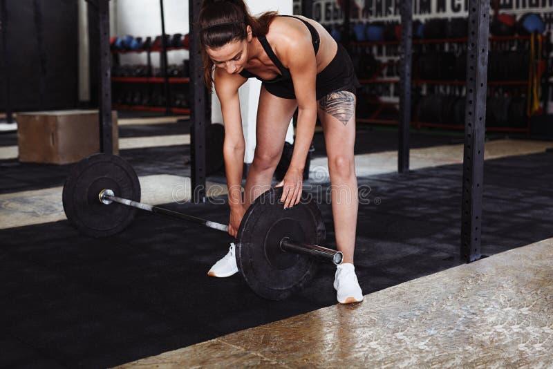 Stark ung kvinna som justerar vikt på skivstång arkivbild