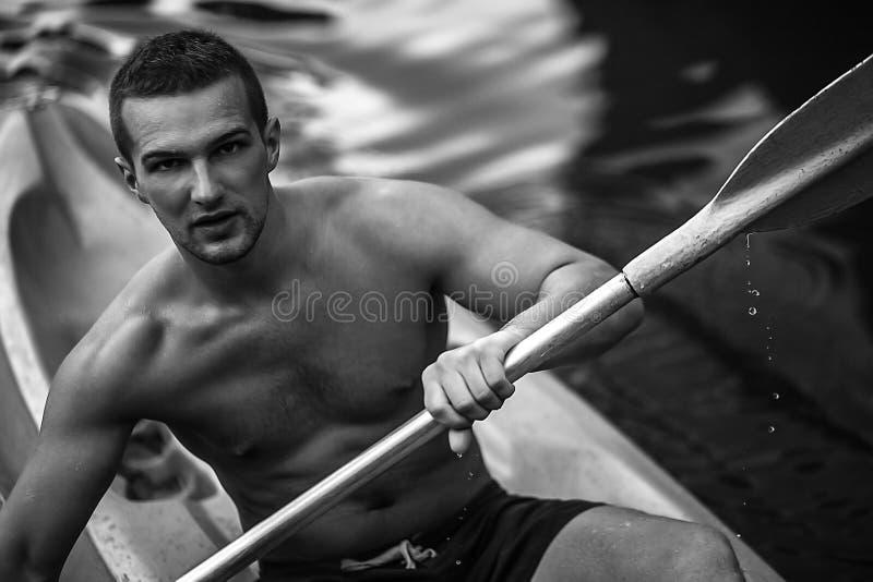 Stark ung man i kajak på den pittoreska sjön i Thailand. royaltyfri fotografi