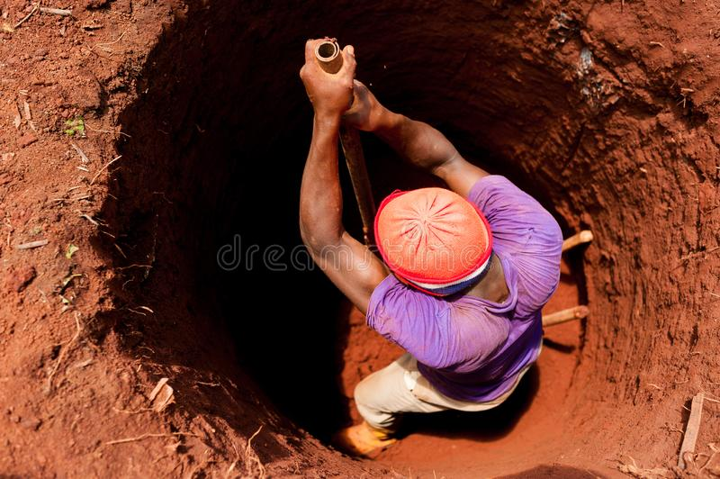 Stark ung pojke som manuellt väl gräver med skyffeln i afrikansk liten by med röd jord royaltyfria bilder