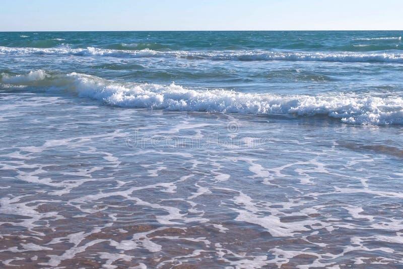 Stark våg för stormhav med skum på den sandiga stranden royaltyfri fotografi