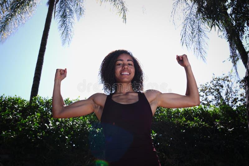 Starka krullande armar för ung kvinna som visar biceps royaltyfri foto