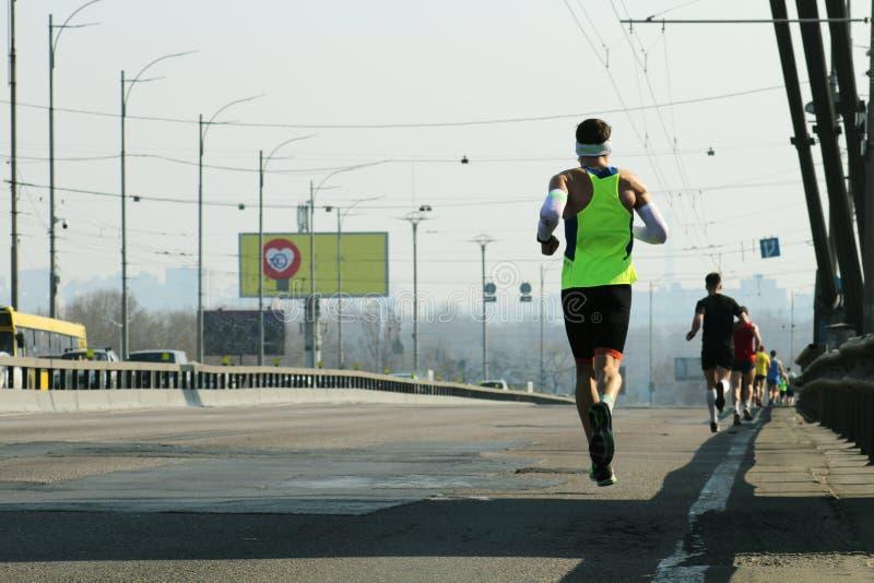 Starka l?pare som k?r p? stadsbrov?gen K?ra p? stadsbron Maratonspring i morgonen Spring f?r idrottsman nenl?parefot royaltyfri bild