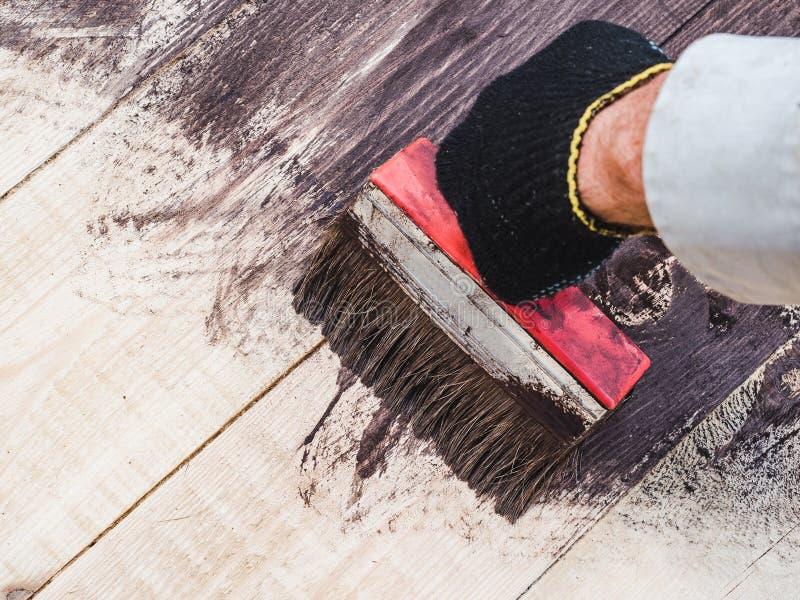 Starka manliga händer som målar träbräden closeup arkivbilder
