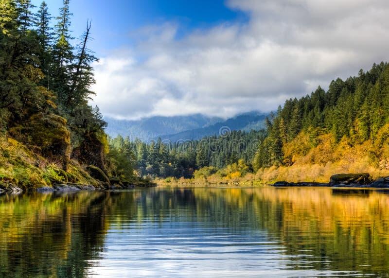 Starka mossiga stenblock fodrar kanterna av den lägre Rogue River i sena Oktober med blå himmel och moln i avstånd royaltyfria foton