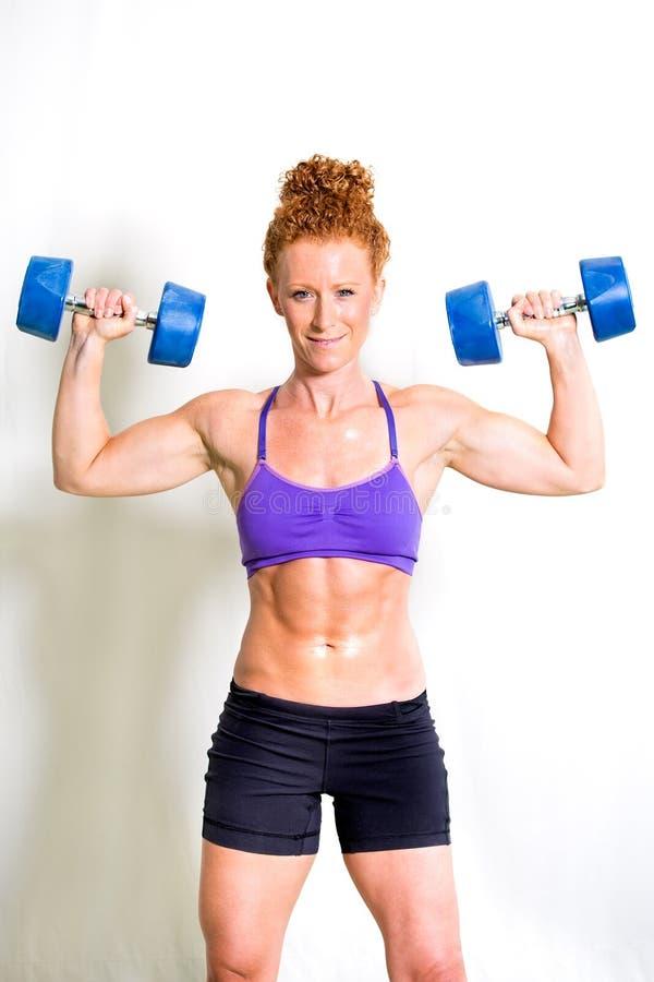 Starka muskulösa lyftande vikter för ung kvinna fotografering för bildbyråer