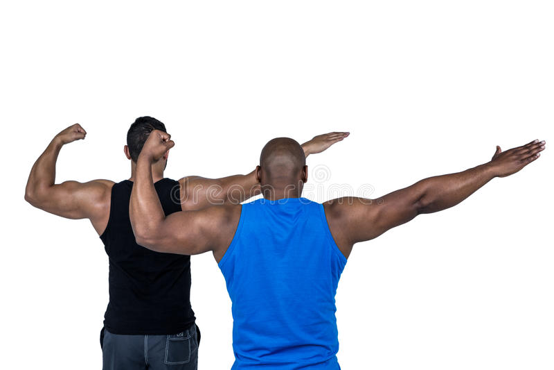 Starka vänner som poserar med armar ut royaltyfri fotografi