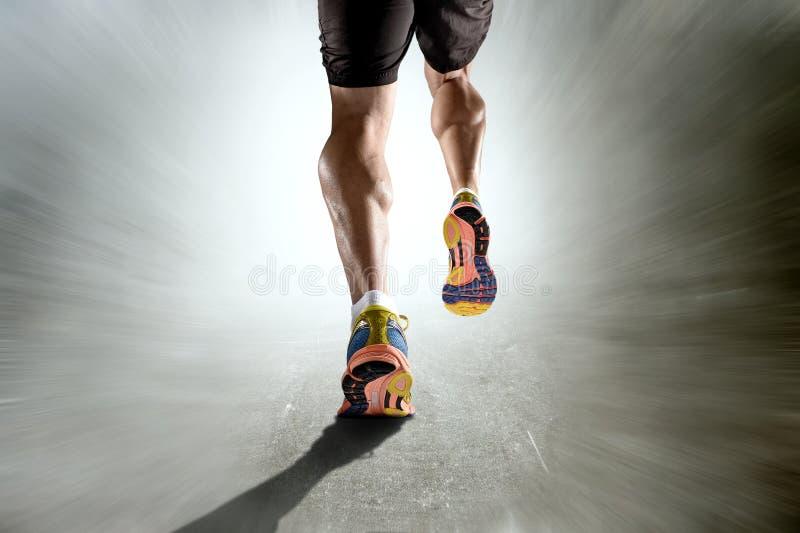 Starke athletische Beine mit dem zerrissenen Wadenmuskel des Sportmannes laufend auf Bewegungsschmutzhintergrund lizenzfreies stockfoto