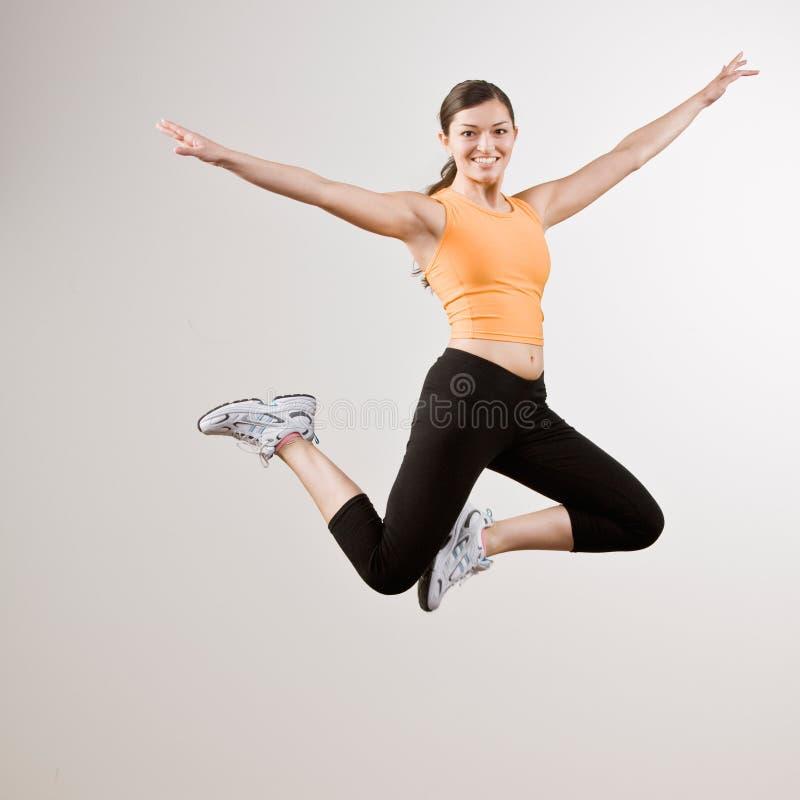 Starke athletische Frau, die in mitten in der Luft springt lizenzfreie stockbilder