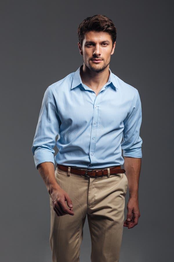 Starke attraktive junge manwalking und schauende Kamera lizenzfreies stockfoto
