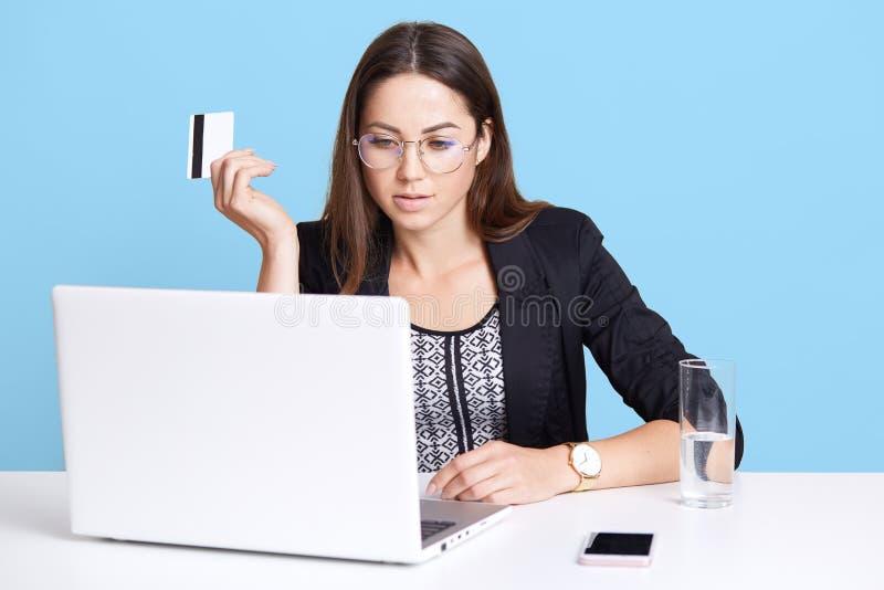 Starke beschäftigte überzeugte Frau sitzt im Büro und arbeitet mit ihrem Laptop und hebt Kreditkarte an und betrachtet Monitor un lizenzfreies stockfoto