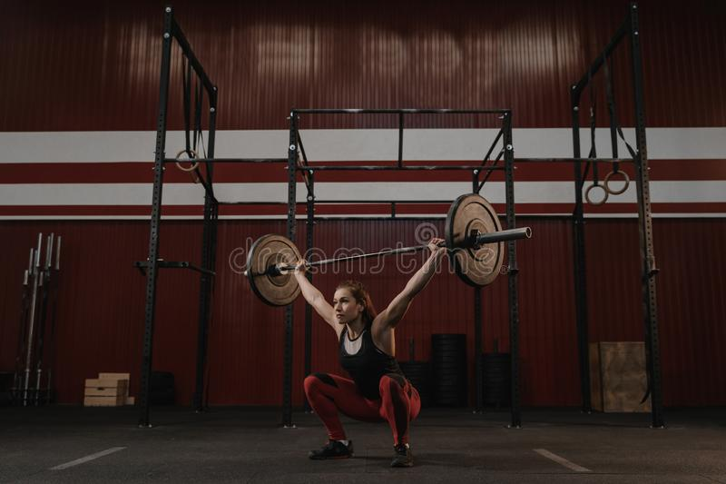 Starke crossfit Frau, die Hocken mit Barbellunkosten tut Geeignete junge Frau, die schwere Gewichte anhebt lizenzfreies stockfoto