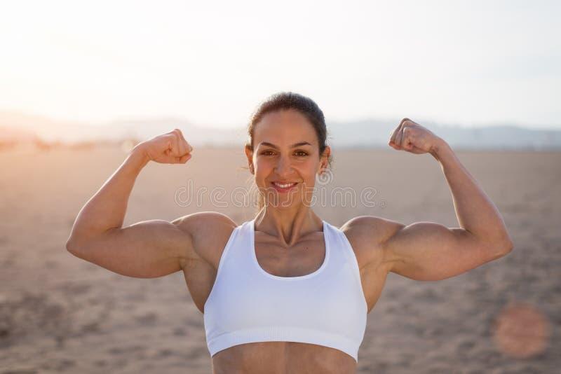 Starke Eignungsfrau, die Bizeps auf Sonnenuntergang biegt lizenzfreies stockfoto