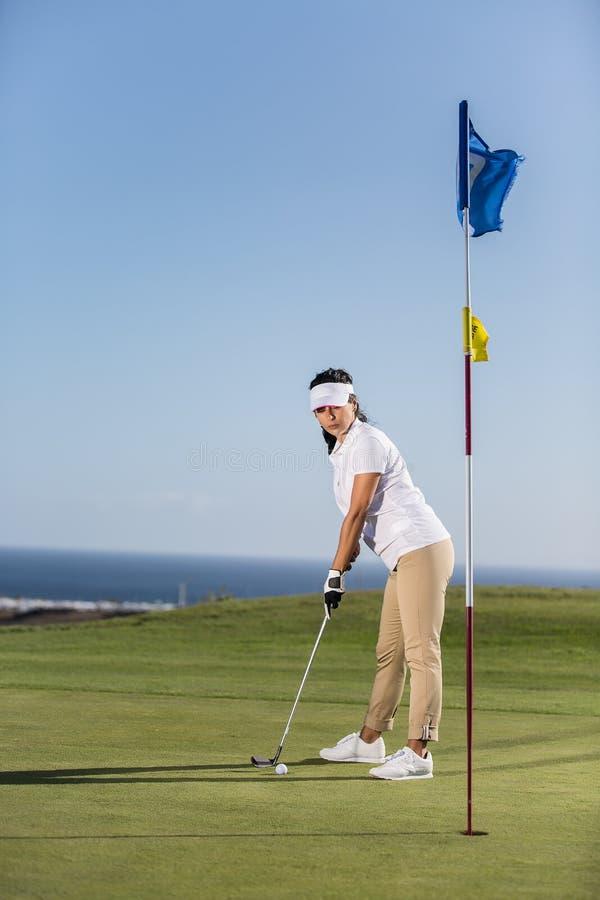 Starke Frau, die Golfball schlägt stockbilder