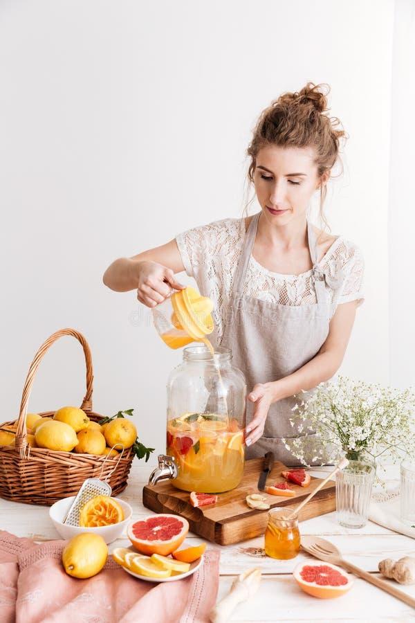 Starke Frau, die zuhause steht, kochend Zitrusfruchtgetränk stockbild