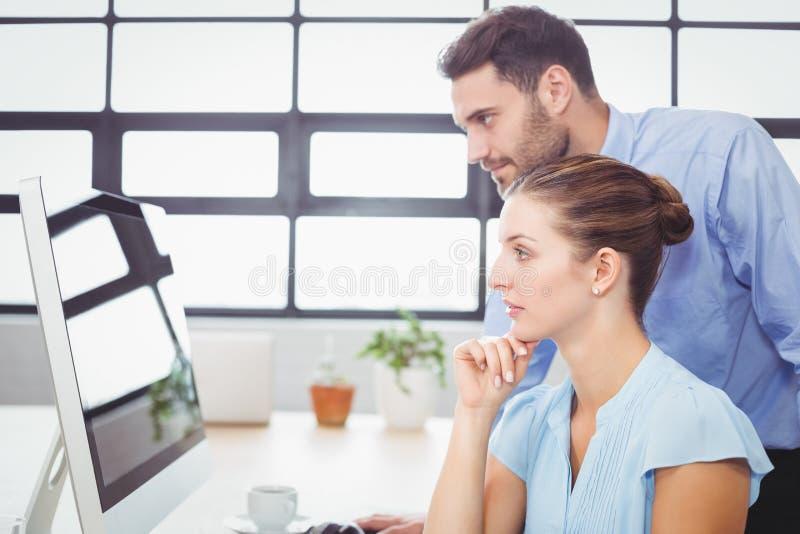 Starke Geschäftsleute, die Computermonitor betrachten stockfotografie