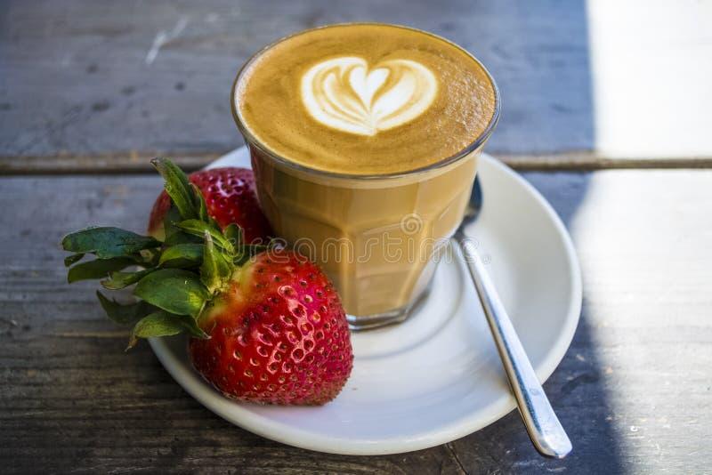 Starke Glastrommel mit Cappuccino und Lattekunst im Formherzen Frische Erdbeere und Kaffee Auf Holz mit Untertasse, Löffel lizenzfreie stockbilder