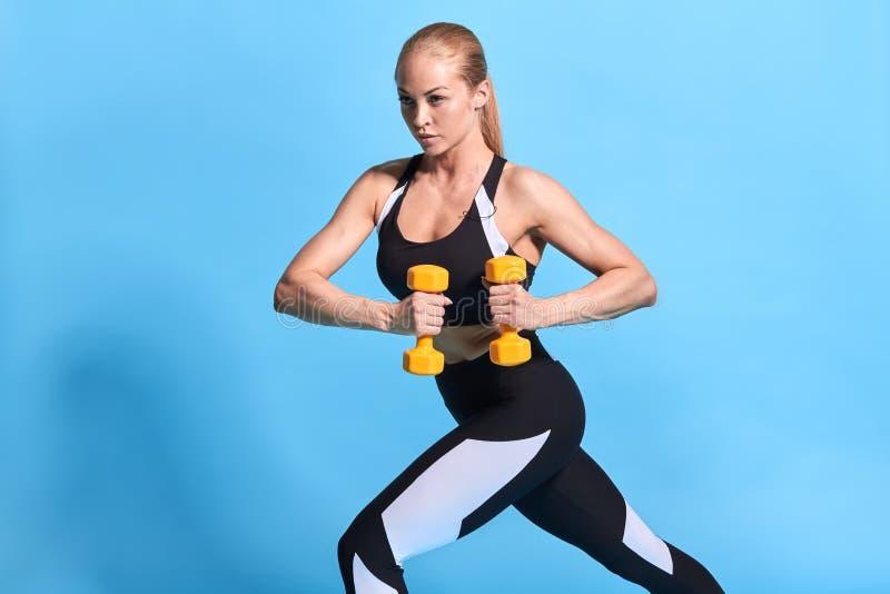Starke hübsche Sportlerin in der stilvollen Sportkleidung ausarbeitend mit Gewicht stockbilder