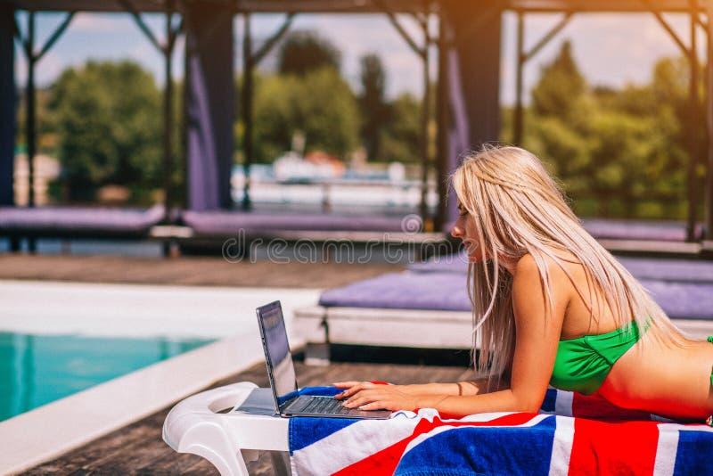 Starke junge Frau Blondie legt auf den Klappstuhl und schreibt auf ihrem Laptop nahe dem Pool lizenzfreie stockfotos