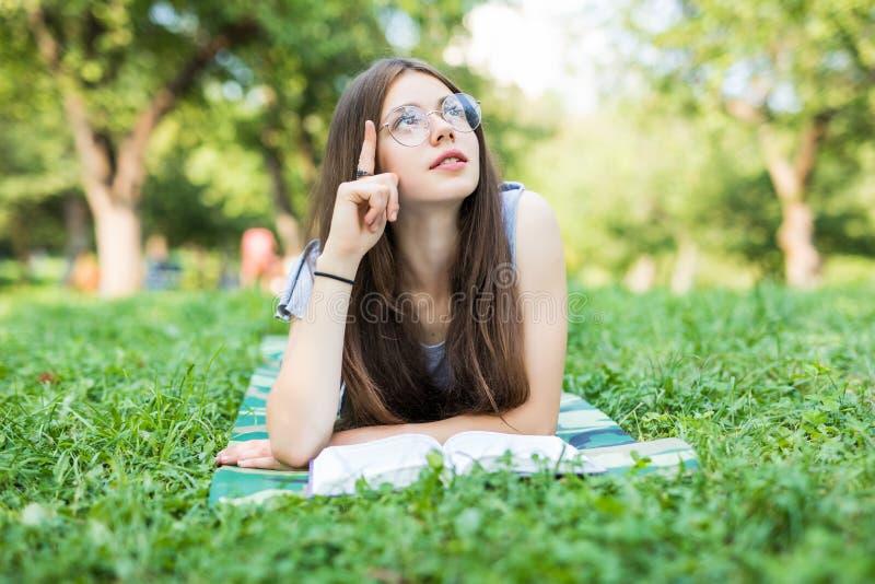 Starke junge Frau, die beim Buch im Park liegt Ernstes schönes Mädchen, das auf Gras beim Ablesen Lieblingsromanze liegt Träumen stockbild