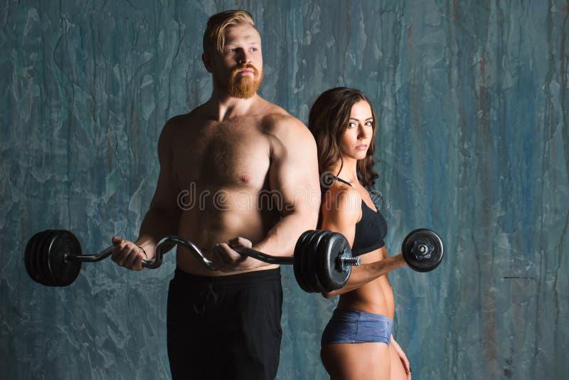 Starke junge Paare, die mit Dumbbells ausarbeiten stockfotos