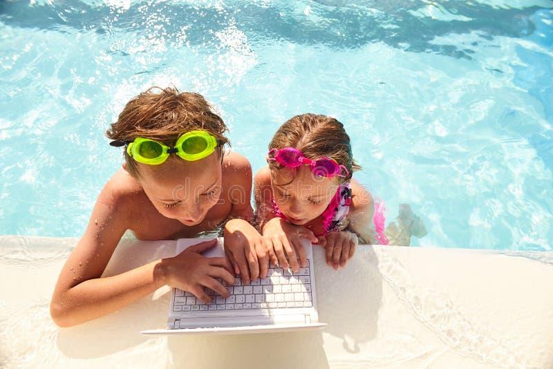 Starke kleine Geschwister, die Laptop im Pool verwenden stockfotos