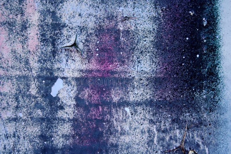 Starke Oberflächenstruktur mit Rest blauer und violetter Farbe auf Betonmauer für abstrakte Hintergründe stockfotografie
