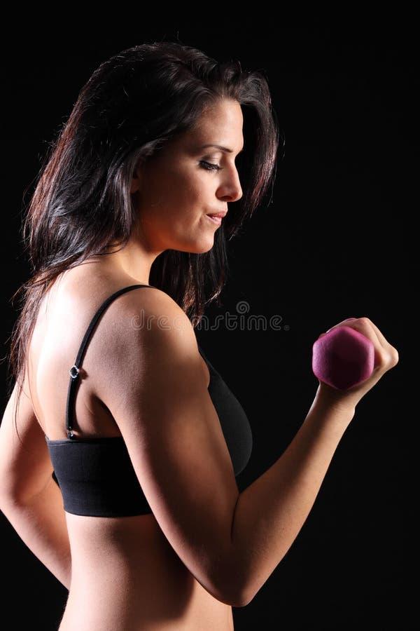 Starke schöne Mädchen bicep Rotationübung in der Gymnastik lizenzfreie stockfotos