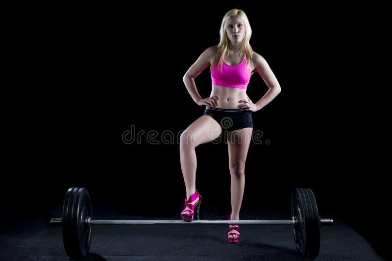 Starke sexy Frauenhaltungen mit Gewicht lizenzfreies stockfoto