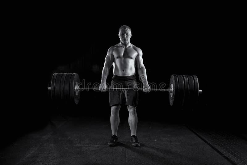 Starke sexy Mann deadlifts viel Gewicht lizenzfreie stockfotografie