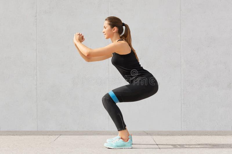 Starke sportliche kaukasische Frau hat Übungen mit Gummiwiderstandband, bildet Beine aus, arbeitet an den Muskeln, gekleidet im T stockfotografie
