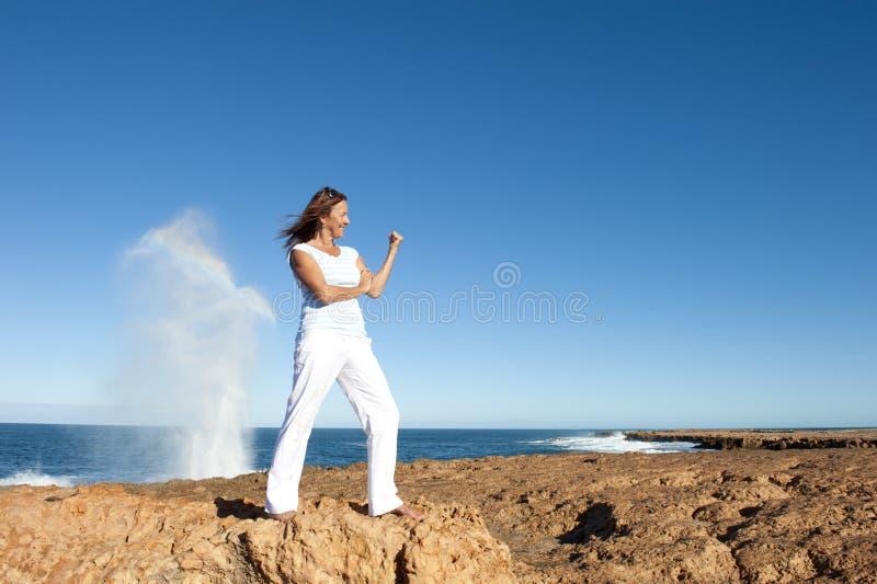 Starke und überzeugte Frau am Ozeanhintergrund stockfotografie
