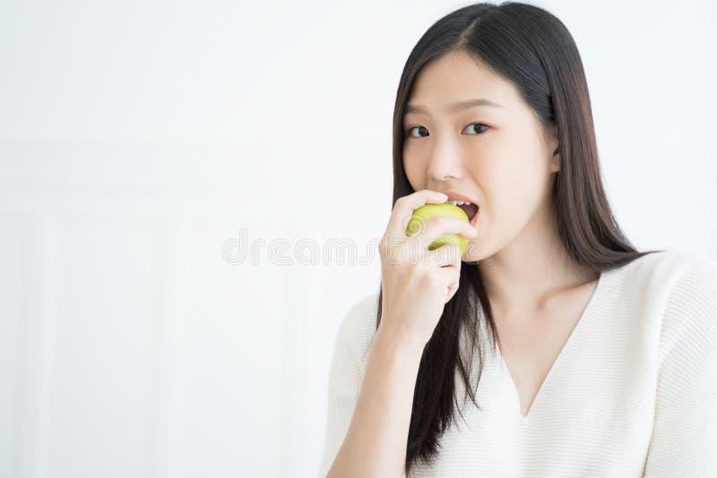 Starke Zähne der jungen Asiatinbissgrünapfel-Show lizenzfreie stockfotografie