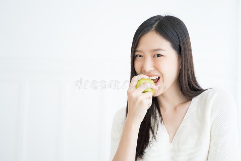 Starke Zähne der jungen Asiatinbissgrünapfel-Show lizenzfreie stockfotos