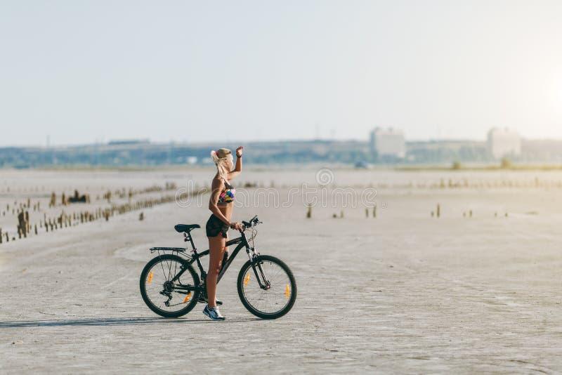 Starken Blondine in einer mehrfarbigen Klage sitzen auf einem Fahrrad in einem Wüstengebiet und betrachten die Sonne Entspannung  stockfotos