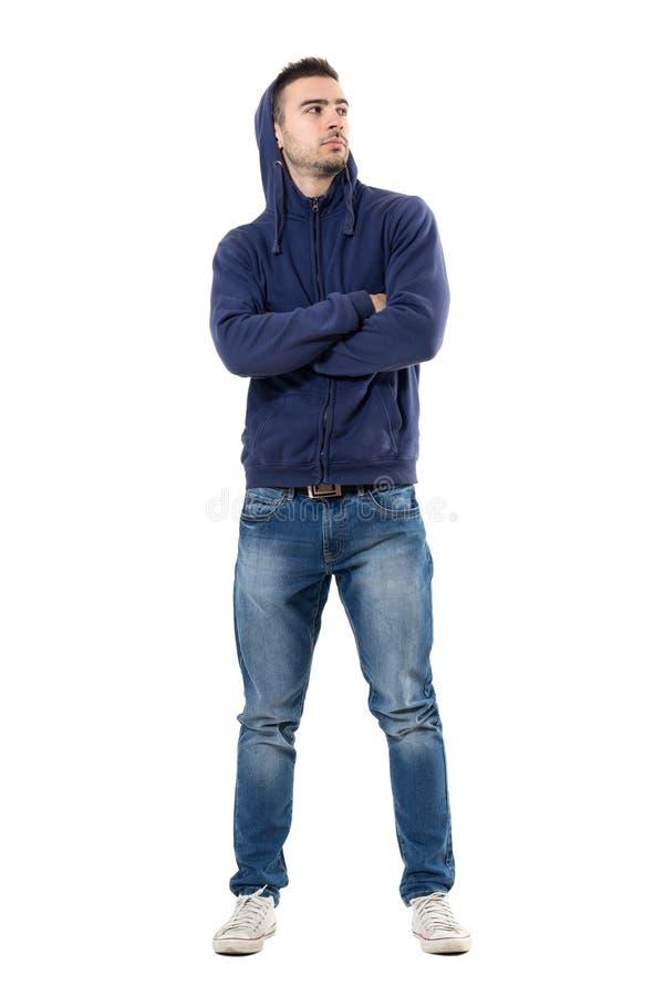 Starker überzeugter junger Mann mit Hoodie auf dem Kopf und gekreuzten Armen, die oben schauen stockfoto