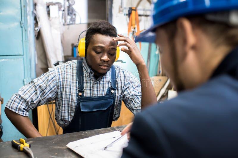 Starker Arbeiter, der auf Plan des Chefs hört lizenzfreies stockbild