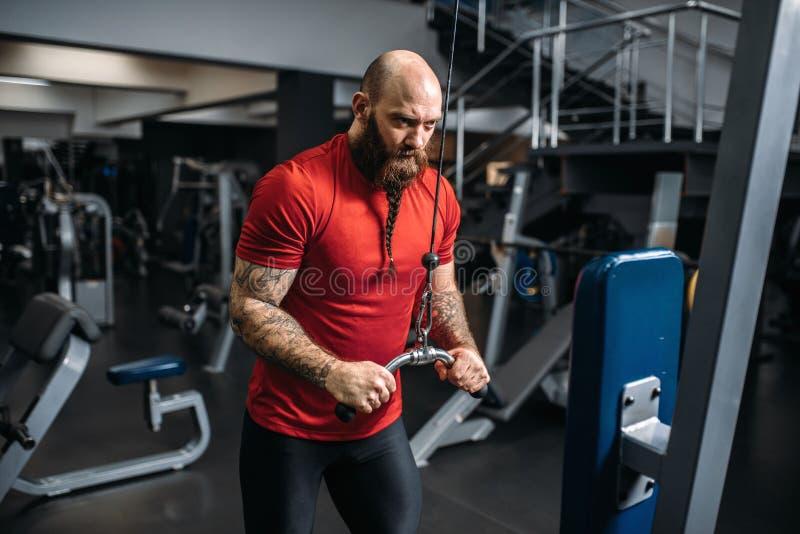 Starker Athlet, bildend auf Übungsmaschine aus lizenzfreie stockfotos