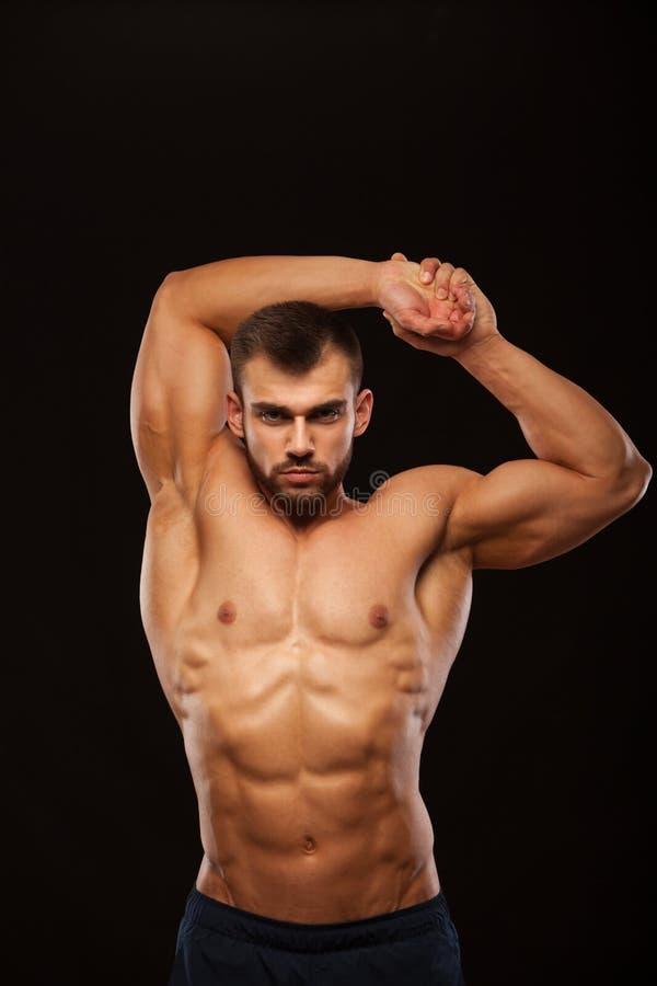 Starker athletischer Mann - Eignungs-Modell zeigt seinen Torso mit sechs Satz-ABS und hält seine Hände hoch Lokalisiert auf Schwa stockfotos