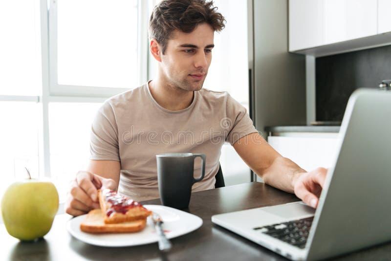 Starker attraktiver Mann, der Laptop beim Essen des Frühstücks verwendet lizenzfreie stockbilder