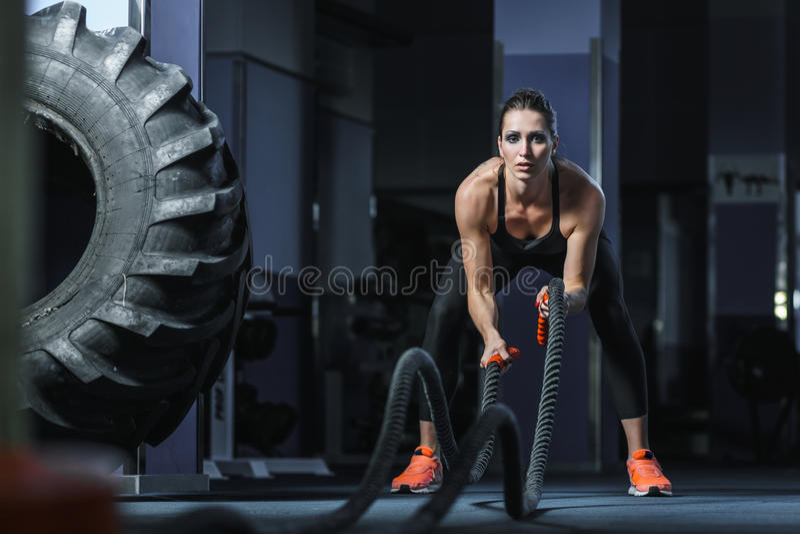 Starker attraktiver muskulöser CrossFit-Trainer kämpfen Training mit Seilen lizenzfreies stockfoto